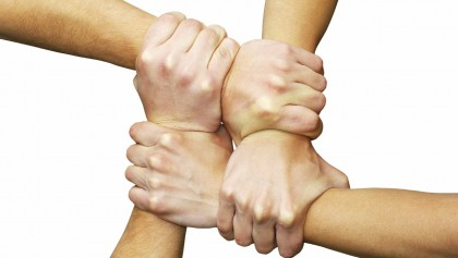 Linked hands on a white background symbolizing teamwork and friendship